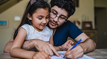 Handsome Latino man is sitting at a desk with daughter in his lap and signing papers.